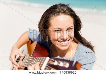 Beautiful young woman playing guitar on beach