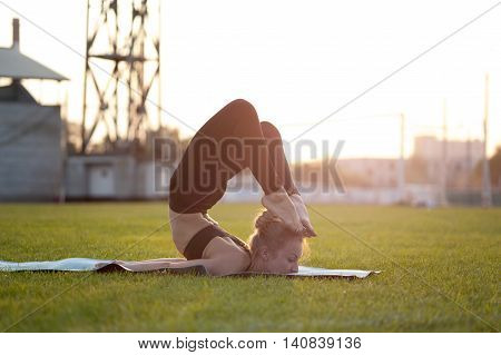Young flexible woman doing yoga exercises on green grass. Scorpion Pose Chest Stand Head to Foot.