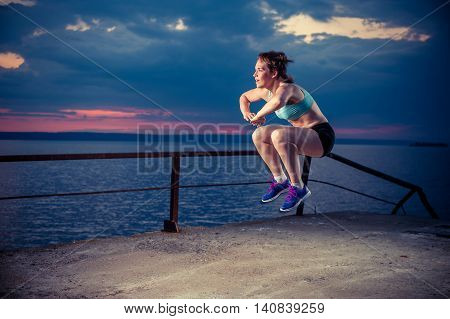 Young strong woman in sportswear doing plyometric exercises on pier. Jump squats fitness workout outdoors.