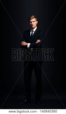 Full-length portrait of business man  isolated on black backgrou