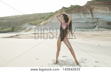 Sexy brunette Woman in black swimsuit with long black hair and red lips on the background of sands career