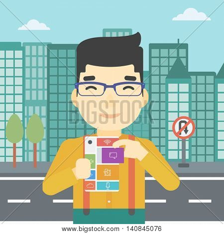 An asian man holding modular phone. Young man with modular phone on a city background. Man using modular phone. Vector flat design illustration. Square layout.