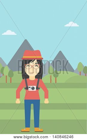 An asian woman with a digital camera on her chest. Tourist with a digital camera standing on the background of mountains. Vector flat design illustration. Vertical layout.