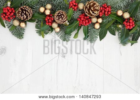 Christmas abstract background  border with flora of holly, ivy, gold baubles and pine cones with snow covered winter greenery over distressed white wood.