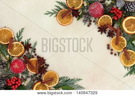 Christmas abstract background border with dried fruit and spice, holly, mistletoe and snow covered cedar cypress on old parchment paper.