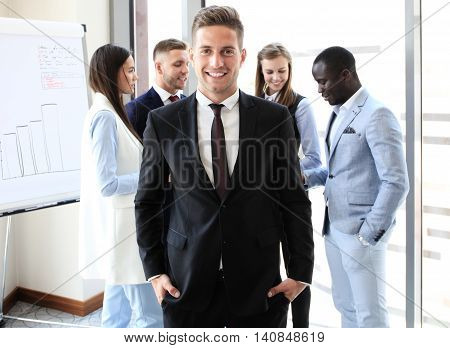 Happy smart businessman with team mates discussing in the background