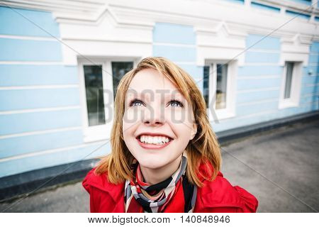 Closeup portrait of cheerful young woman smiling in the street