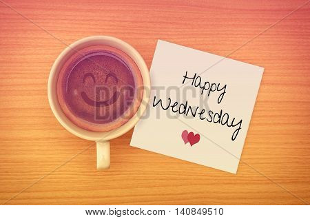 Happy Wednesday on paper note with coffee cup,top view.