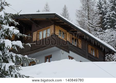 idyllic snowed house with icicles in the woods