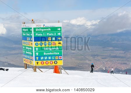 Bansko, Bulgaria - March 4, 2016: Ski resort Bansko, Bulgaria aerial view, skiers, signpost with ski slopes directions