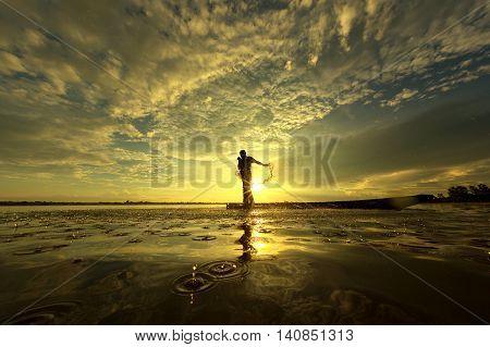 Silhouette fisherman net water splash on the boat in LakeWanon niwatsakon nakon Thailand