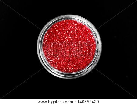 Red shiny sparkling eye shadow in jar isolated on black background