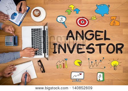 ANGEL INVESTOR Business team hands at work with financial reports and a laptop