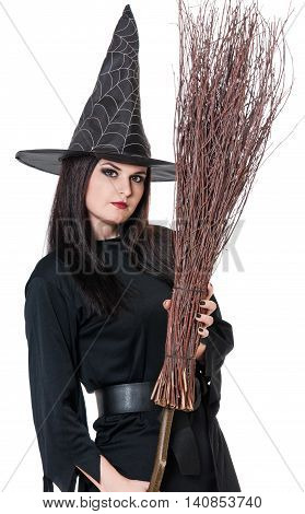 Young witch with broom isolated on white background