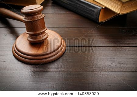 Judge hammer with old legal book on brown lacquered wooden desk close up with copy space. Legislation Concept