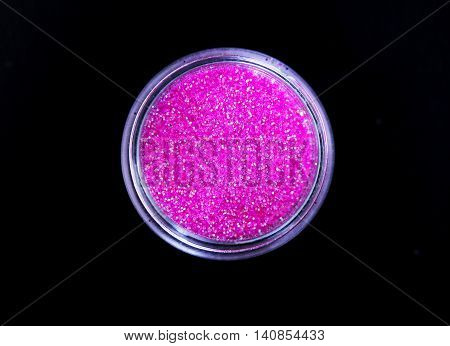 Pink shiny sparkling eye shadow in jar isolated on black background