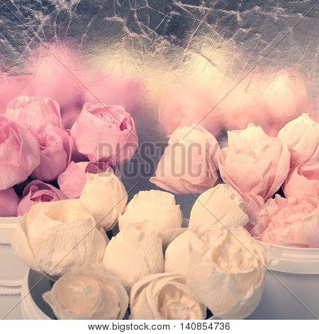 Art paper flowers in buckets of pink, yellow, beige
