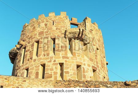Old crenellated towers with loopholes on sky background