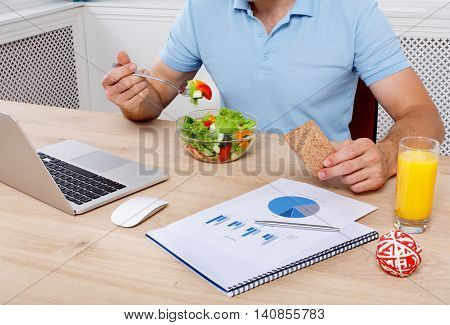 Unrecognizable man has healthy business lunch in modern office. Businessman in t-shirt at working place with vegetable salad in bowl and fork in hand, diet and eating right concept.