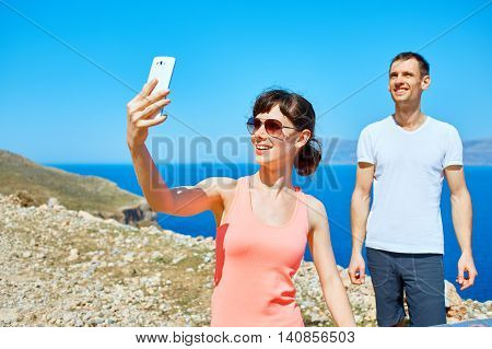 couple on the sea beach at the morning. woman taking a selfie
