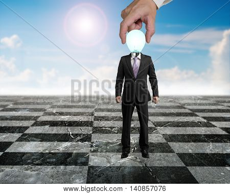 Hand Putting Man With Lamp Head In Chess Game