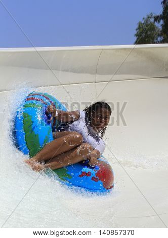 Rhodes Greece-July 26 2016:Black cheerful girl drive with tube on the rafting slide in the Water park.Rafting slide is one of many popular game for adults and children in park. Water Park is located on the island of Rhodes in Greece