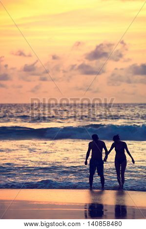 Seascape beautiful sunset beach with silhouette couples together.