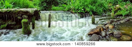 Panoramic image of the forest waterfall in the summer