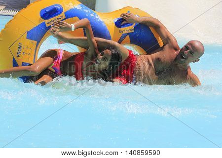 Rhodes Greece-July 29 2016:Father and  daughter  after rafting slide in the Water park.Rafting slide is one of many popular game for adults and children in park.Water Water Park is located on the island of Rhodes in Greece