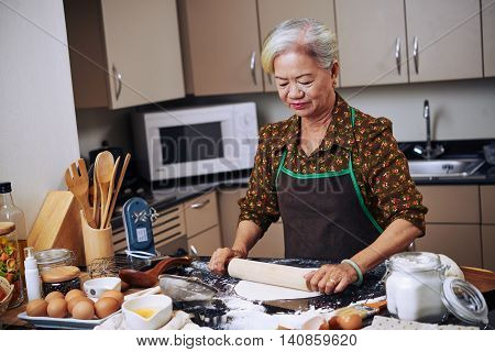 Senior Vietnamese woman cooking in her kitchen