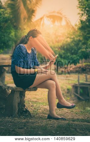 Abstract scene of young woman using her smartphone seriously while sitting outdoor on wood chair in morning time on weekend. Phone addiction abstract concept with vintage filter effect