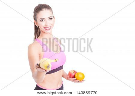Young Woman Wearing Sportswear At Gym Holding Fruits