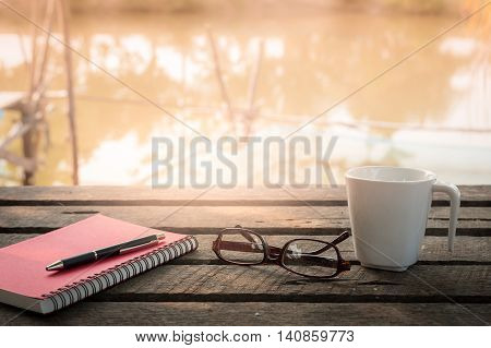 Morning lifestyle scene. Pen opened notebook glasses and coffee cup on outdoor wood table in morning time on weekend. Freelance business working concept