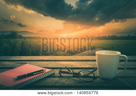 Pen opened notebook glasses and coffee cup on outdoor wood table in morning time on weekend with sunrise landscape view in blurry background. Weekend morning lifestyle concept with vintage filter effect