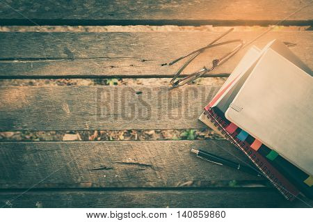 Pen opened notebook glasses and coffee cup on outdoor wood table in morning time on weekend. Freelance business working lifestyle concept with vintage filter effect