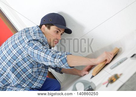 man removing masking tape from skirting board