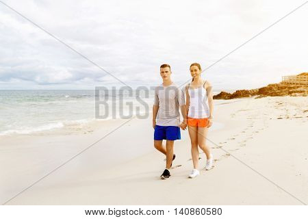 Runners. Young couple running on beach