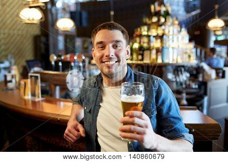 people, drinks, alcohol and leisure concept - happy young man drinking draft beer at bar or pub counter