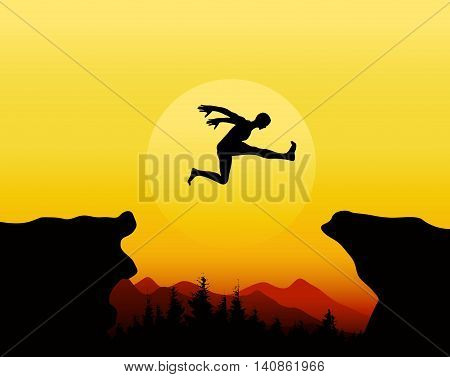 silhouette of man jumping on cliff  with sunset background
