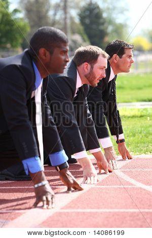 Businessmen lined up on track starting line