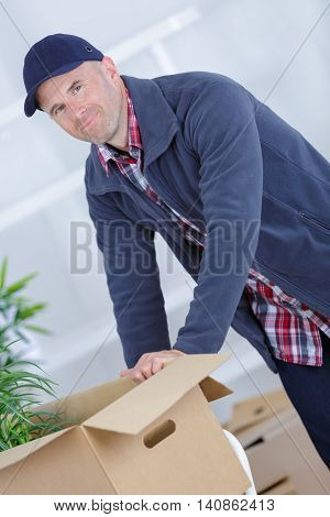 happy smiling delivery man carrying boxes