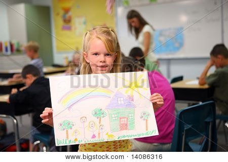 Elementary school student holding up drawing