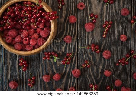 Fresh berries raspberry and red currant in bowl on wooden table