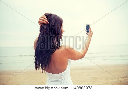 summer, travel, technology and people concept - sexy young woman taking selfie with smartphone on beach from back