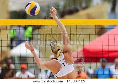 Volleyball player is a female athlete beach volleyball player rising up to make a play on the ball.