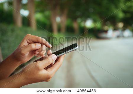 close up hand using phone on street