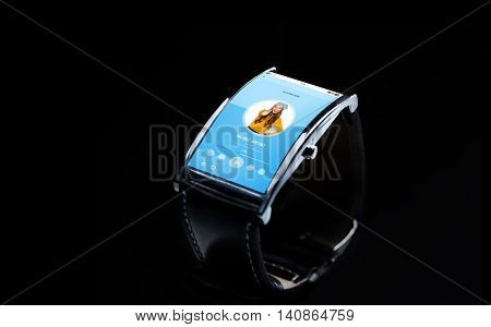 modern technology, object and media concept - close up of black smart watch with music player on screen