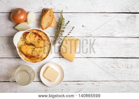Onion soup with its ingredients on the white table (traditional french cuisine)