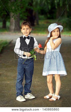 Small romantic kids walking in park