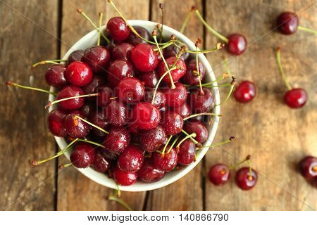 Bowl with fresh ripe cherries on wooden background